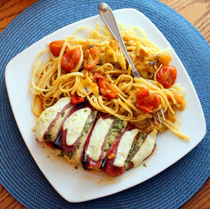 Chicken Antipasti. Baked chicken smothered in pesto topped with salami and mozzarella.  This delicious entree is also complimented with a cherry tomato and artichoke sauce! Yum!  Small Town Girl Blog.